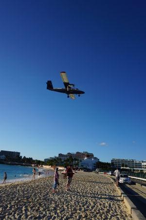 Lietadlo pristáva ponad pláž Maho na letisku princeznej Juliany na ostrove Svätý Martin