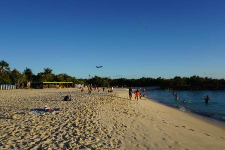 Pláž v zálive Mullett Bay - v pozadí vzlieta lietadlo z medzinárodného letiska princeznej Juliany