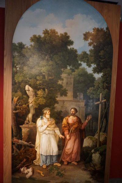 Obraz symbolizujúci prechod ku kresťanstvu - druid a sv. Exupéry (vierozvestca v Bayeux) a pod ich nohami zničené modly symbolizujúce starú vieru - Múzeum umenia a histórie baróna Gérarda (MAHB) v Bayeux