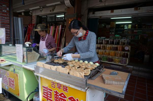 Pouliční predajcovia na ulici Dihua v Tchaj-peji ponúkajú rôzne pochúťky