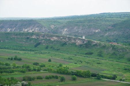 Zelené údolie Butuceni, v skale vidieť diery jaskýň, nad ňou nový kláštor