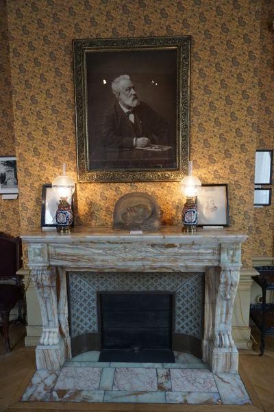 Krb a nad ním obraz Julesa Verna v jeho dome v Amiens - na krbe je taktiež položná jeho posmrtná maska