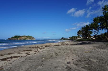 Pláž s čiernym pieskom v mestečku Sainte-Marie, v pozadí ostrovček Îlet Sainte-Marie
