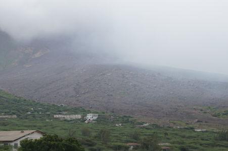 Zlovestný vulkán ukrytý v oblačnom opare, vykúkajú len nánosy popola
