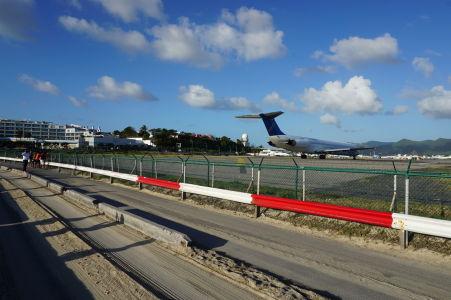 """Lietadlo karibskej spoločnosti InselAir sa pripravuje na štart zatiaľ čo pri plote sa odvážlivci pripravujú na """"jet blast"""""""