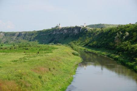 Údolie Butuceni s riečkou Raut - V skale sú vidieť otvory jaskýň starého kláštora, na skale nový kláštor