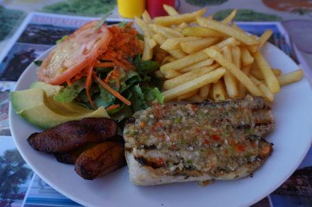 Grilovaná ryba mahi-mahi, obľúbená v celom Karibiku. Karibská kuchyňa často dopĺňa jedlá o malé opečené banány (vedľa ryby)