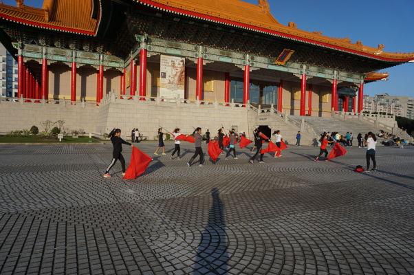 Skupinka mladých cvičí nejakú choreografiu pred Národnou koncertnou sieňou v Parku Čankajškovho memoriálu v Tchaj-peji