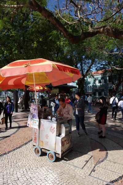 Pouličný predavač na námesti Barra v Macau
