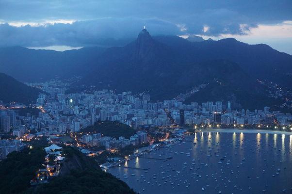 Pohľad na Rio de Janeiro pri západe Slnka z Cukrovej homole - v strede hore na Corcovade svieti Socha Krista Vykupiteľa
