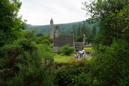 Pohľad na kláštorné mesto Glendalough od vstupu k nemu. Najznámejšie dve stavby - Kruhová veža a Kostol sv. Kevina