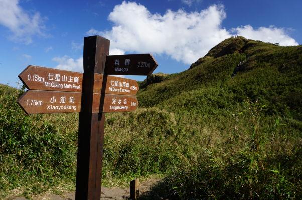 Turistický chodníček v Národnom parku Yangmingshan vedúci na vrchol hory Qixing, viditeľný v pozadí
