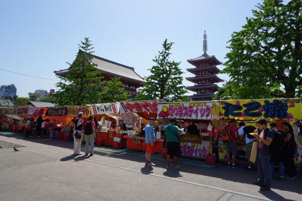 Stánky s jedlom v areáli chrámu Sensó-dži (Senso-ji) v Tokiu, v pozadí hlavná hala a typická päťposchodová pagoda