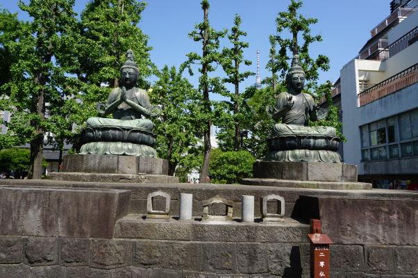 Sochy Budhu v chráme Sensó-dži (Senso-ji) v Tokiu, v pozadí vidieť vežu Tokyo Skytree