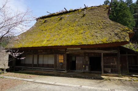 Drevený dom s machom porastenou strechou v skanzene Hida no Sato