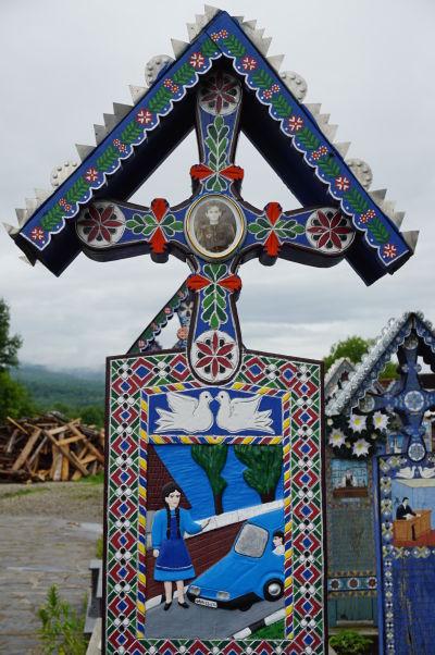 Veselý cintorín v Săpânțe - Náhrobok vyobrazuje dievča, ktoré zrazilo auto. Je dokonca vidieť i evidenčné číslo vozidla, ktoré ju zrazilo