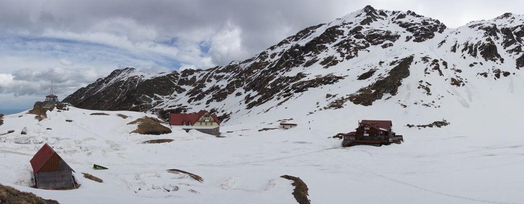 Najvyšší bod Transfagarašanu a okolie jazera Balea býva pod snehom i na začiatku leta - panoramický záber na kaplnku a horské chaty