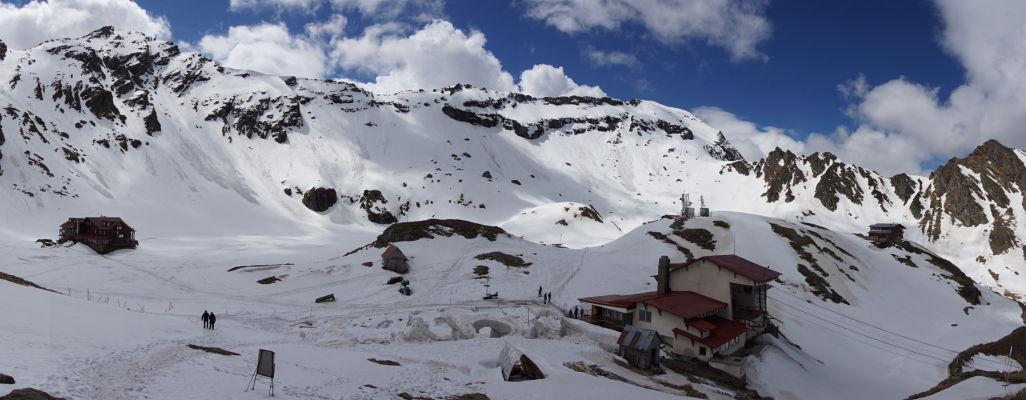 Okolie cesty Transfagarašan v najvyšších rumunských horách - vpravo horná stanica lanovky, vľavo horská chada a okolo nej zamrznuté jazero Balea