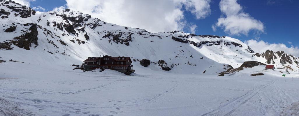 Horská chata na ľadovcovom jazere Balea, ktoré je pokryté snehom a ľadom aj na začiatku leta - všetka rovná plocha bude v júli vodnou hladinou