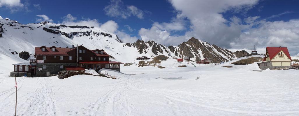 Horské chaty  a medzi nimi ľadovcové jazero Balea pokryté snehom a ľadom na začiatku leta v najvyšších rumunských horách - všetka rovná plocha bude v júli vodnou hladinou