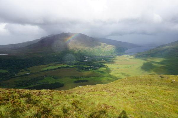 Pohľad z Diamantovej hory (Diamond Hill) na jazero Kylemore Lough v národnom parku Connemara National Park v Írsku - v diaľke zhruba pod malým kúskom dúhy je vidieť kláštor Kylemore Abbey