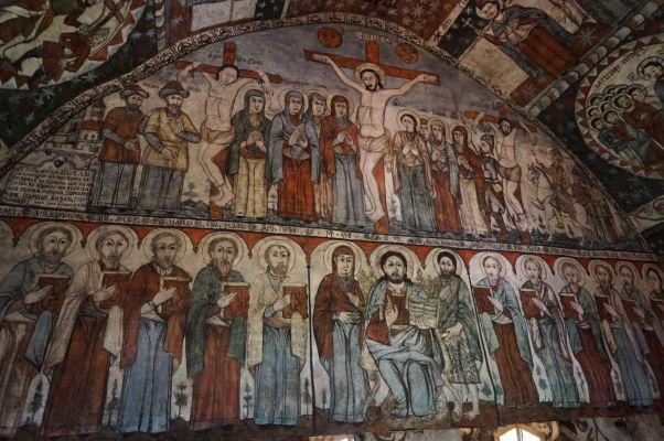Krásne maľovaný interiér dreveného kostolíka v skanzene v Sibiu - ukrižovanie a apoštoli
