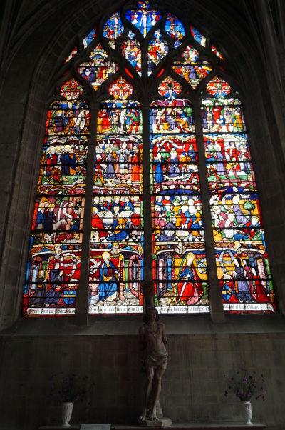 Farebné vitrážové okno a socha sv. Sebastiána v Kostole sv. Magdalény (Église Sainte-Madeleine) v Troyes