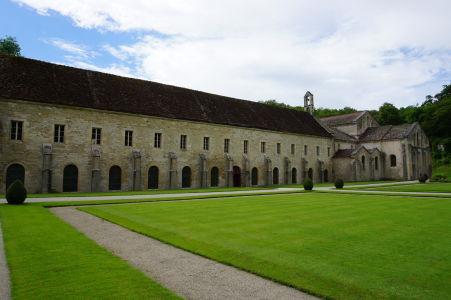 Vľavo dlhá budova ubytovne, vpravo čelo kostola, medzi nimi zvonica