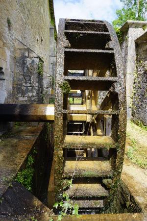 Vodou poháňané mlynské kolo, ktoré poháňa kladivo