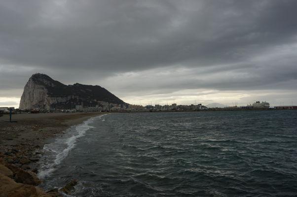 Gibraltarská skala zo španielskeho pobrežia, napravo od nej mesto Gibraltár a úplne vpravo výletná loď