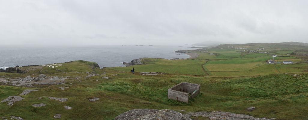 Drsné pobrežie na Malin Head na severe Írska - v popredí zvyšok vojenského bunku, v pozadí uprostred pláž s polodrahokamami Ballyhillin Beach