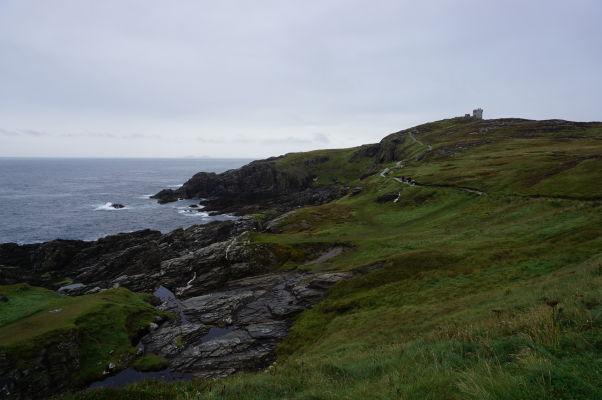Drsné pobrežie na Malin Head na severe Írska - v pozadí vidieť vežu na Banba's Crown