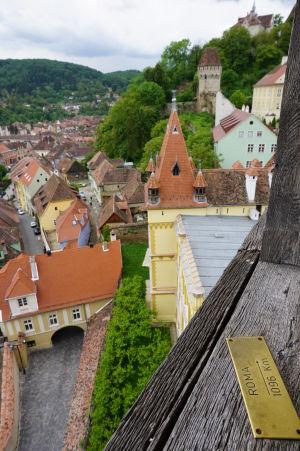Na zábradlí balkóna sa nachádzajú štítky označujúce smer a vzdialenosť k niektorým svetovým mestám