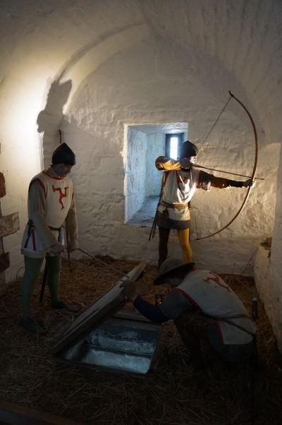 Jedna z vnútorných expozícií na hrade Rushen v Castletowne na ostrove Man, ktorého symbol majú vojaci na hrudi a chrbte