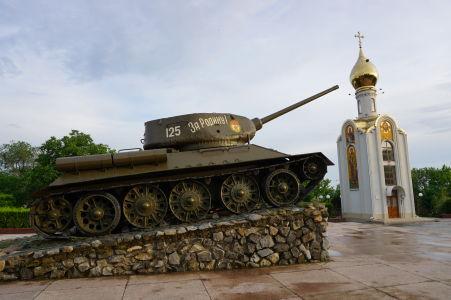 """""""Tankový"""" pamätník s nápisom """"Za rodinu!"""", v pozadí ortodoxná kaplnka"""