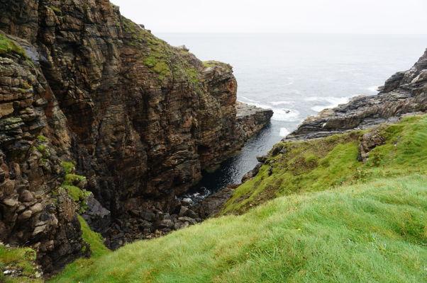 Drsné pobrežie na Malin Head na severe Írska - aj napriek nepriaznivému počasiu je voda priezračne čistá