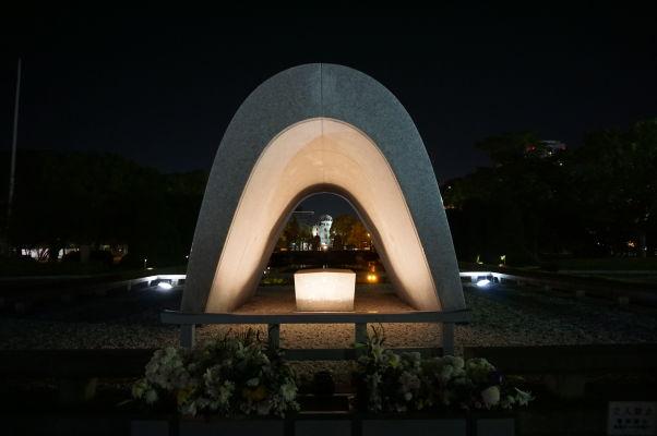 Hrob neznámeho vojaka v Parku mierového memoriálu v Hirošime v noci, v pozadí Atómový dóm