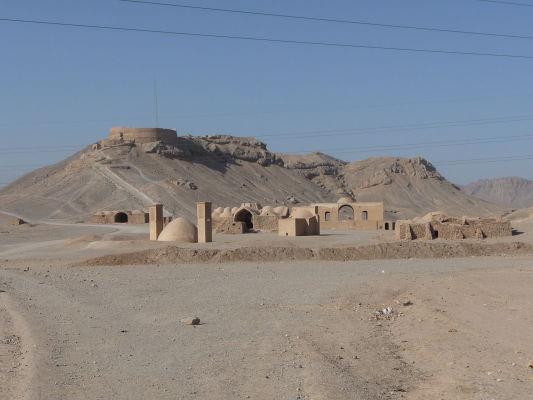 Vzadu na kopci Veža mlčania, v popredí pár starších a dnes už nepoužívaných stavieb na okraji Yazdu