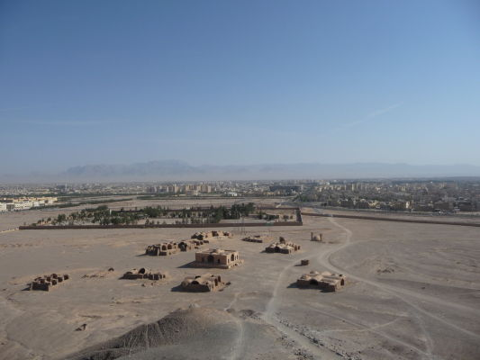 Pohľad na Yazd z Veže mlčania, v popredí pár starých opustených stavieb vrátane starej vodnej podzemnej nádrže
