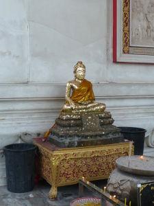 Soška Budhu pred chrámom - Ľudia si kupujú zlaté lupienky, ktoré na sošky nalepujú
