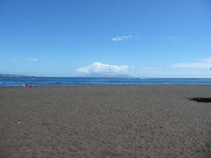 Pláž s čiernym pieskom, v pozadí obrysy ostrova Moorea