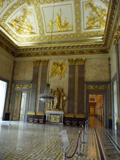 Empír, označovaný aj ako neskorý neoklasicizmus, dominuje tejto veľkej miestnosti v kráľovskom paláci Reggia di Caserta