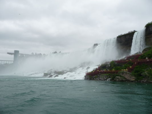 Americký vodopád (American Falls) v strede a malý Nevestin závoj (Bridal Veil Falls) vpravo sú súčasťou Niagarských vodopádov - pohľad z lode na rieke, vľavo vidieť vyhliadkovú plošinu na americkej strane