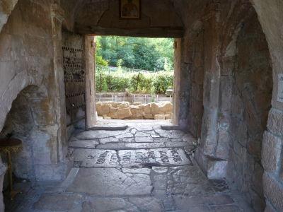 Brána do kláštora, na zemi náhrobný kameň kráľa Dávida IV. Staviteľa