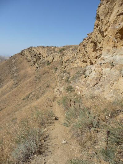 Chodníček po ktorom chodia návštevníci kláštora Davida Garedžu - skala vpravo je posiata celami a svätyňami, ktoré sú do nej vyhĺbené