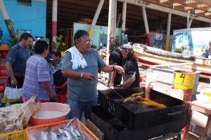 Rybí trh Caleta Portales vo Valparaíse - Predajca ponúka čerstvo smažené ryby