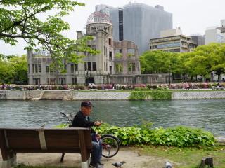 Starček kŕmi vrabce pred budovou zničenou atómovou bombou v Hirošime